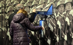 Visitors look at a wall with photographs of soldiers GDR Museum