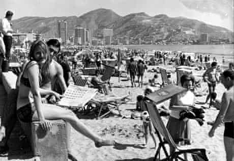 1960's, Benidorm, Spain, A general view of a continental beach scene, with many people sunbathing