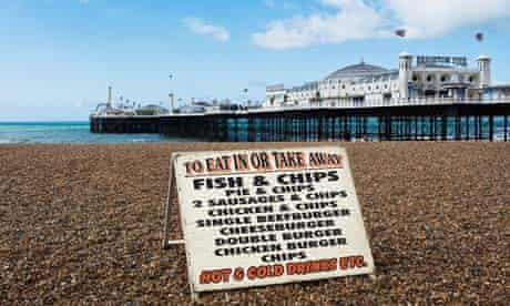 A sign advertising fast food on the shingle beach near the pier in Brighton.
