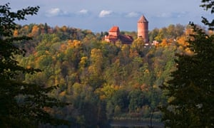 Turaida Castle in Sigulda over autumn forest in Gauja river valley