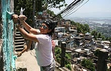 A volunteer painting a favela home