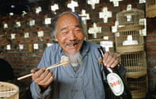 Man eating with chopsticks and drinking beer in China