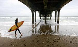A surfer at Boscombe Beach near Bournemouth, DOrset