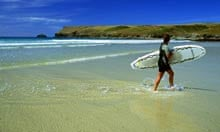 Surfer on the beach at Polzeath in north Cornwall, England