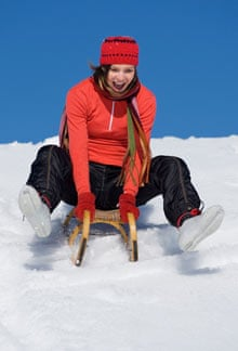 Young woman riding sledge