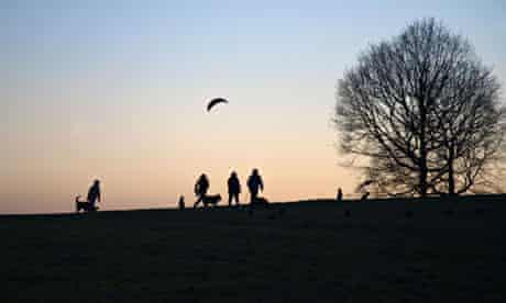 People walking on Hampstead Heath at dusk, London