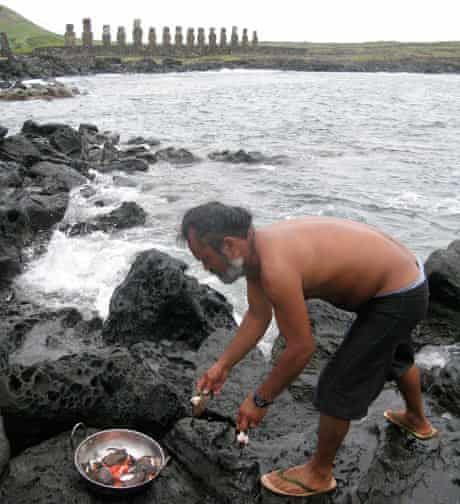 Moi, of Ancestral Tours, cooks fish on a traditional hot-stone fire