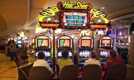 Gamblers trying their luck on the slot machines at Harrah's Casino, Las Vegas