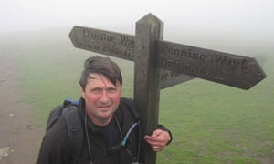Simon clings to a route marker in the rain