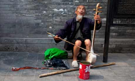 A blind man busking on Yandaixiejie Street which mean Tobacco Pipe Lane.