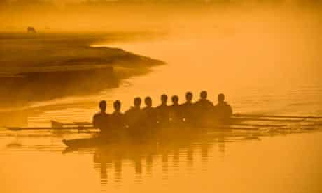 University rowing crew rowing through Port Meadow at sunrise, Oxford, UK