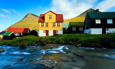 Stream running alongside traditionally built houses in the Faroe Islands