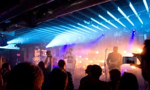 A band plays unders neon lights at Austin's SXSW music festival