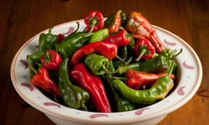 Southwestern style bowl of green and red chili peppers on a rustic wood background.