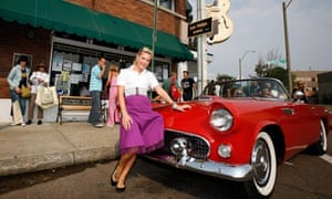 An Elvis fan poses with a convertible in front of Sun Studios in Memphis, Tennessee