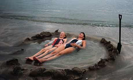 Visitors lie in a home made hot tub at Hot Water Beach in New Zealand
