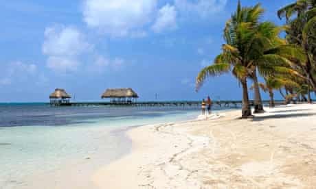 A young couple walking along the beach on the island of Ambergris Caye in Belize