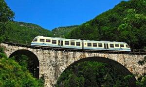 A train on the Centovalli railway crosses a viaduct in Ticino, Switzerland