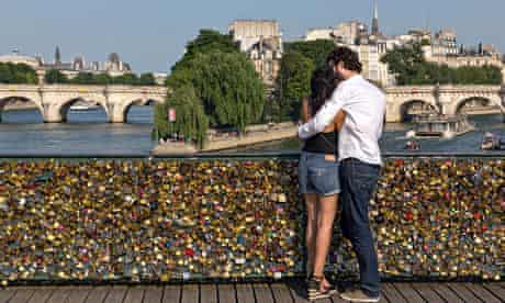 A couple enjoy the view from the Pont des Arts, which is now covered in love locks