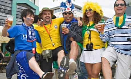Football fans from Japan, Brazil and Argentina drinking beer and dancing together in good mood
