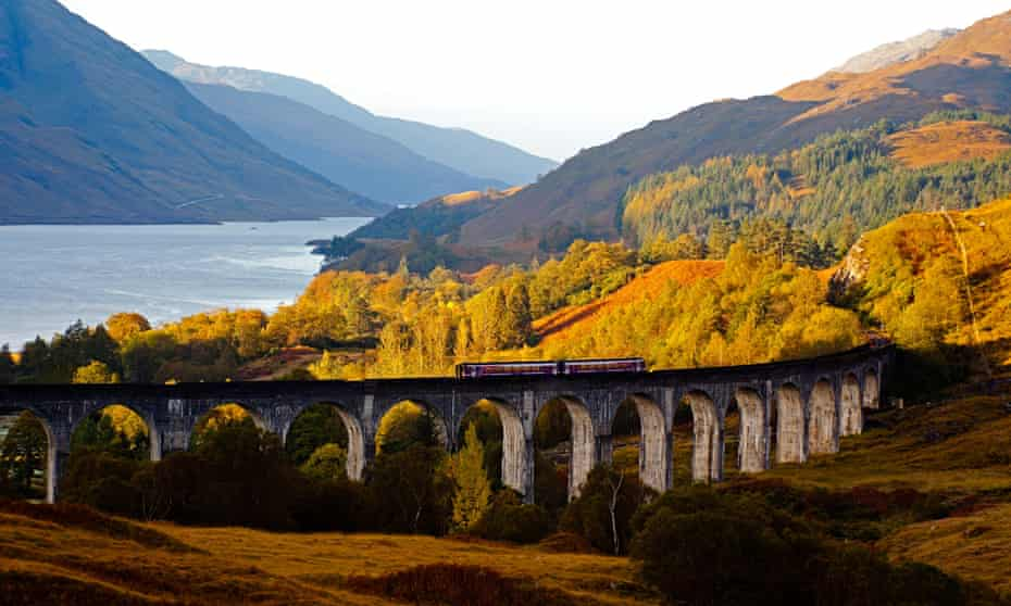 Scotrail train crosses Glenfinnan viaduct with Loch Shiel in background, Lochaber, Scotland, UK