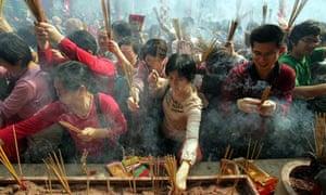 Visitors burn joss sticks and pray at Wong Tai Sin Temple in Hong Kong