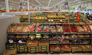 Supermarket shelves stacked with fresh produce