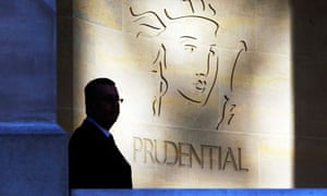 A security guard is silhouetted in front a Prudential office in London