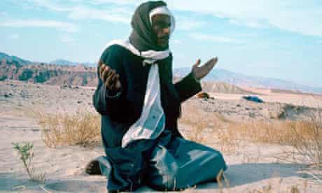 Bedouin man praying to Allah in the desert