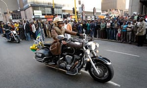 A new age rich black women, riding a Harley Davidson in front of ANC supporters