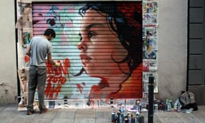 A graffiti artist painting the steel shutter of a hairdresser's in Barcelona