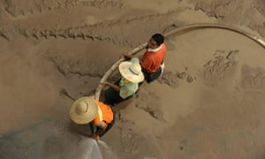 Workers clean up mud left by floods on the banks of the Yangtze River, China