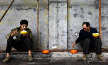 Construction workers eat their lunch at a site in Beijing, China