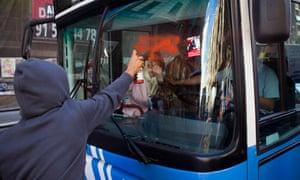 A protestor sprays paint on a public bus driving along Madrid's Gran Via, Spain