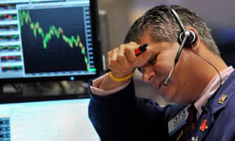 A trader looks at falling share prices in the New York Stock Exchange
