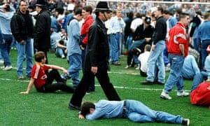 Shocked and injured Liverpool fans lie on the pitch at Hillsborough Stadium on 15 April 1989