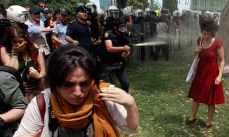 A Turkish policeman uses tear gas on a woman protesting in Gezi Park, Istanbul
