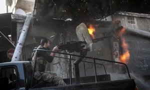 A rebel fighter fires machine gun tin the Jedida district of Aleppo, Syria