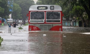 A passenger bus moves through a waterlogged road in Mumbai.