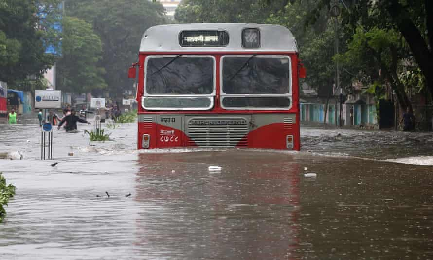 A passenger bus moves through a waterlogged road in Mumbai.